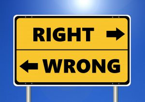 """Road sign with arrow pointing right marked """"Right"""" and arrow pointing left marked """"Wrong"""""""